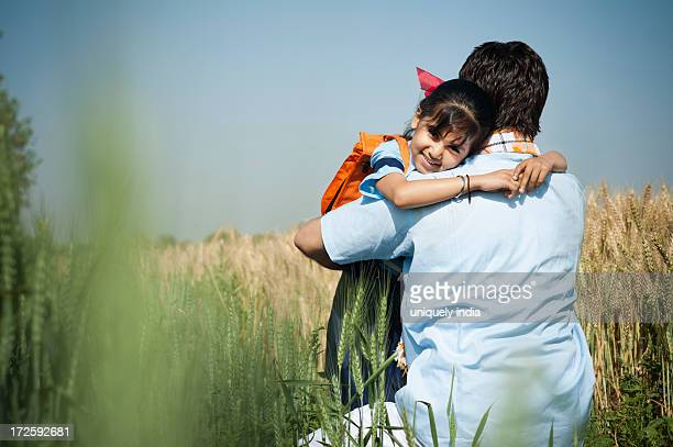 Farmer hugging his daughter in the field