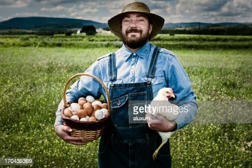 Farmer in blue overalls holding a chicken and basket of eggs