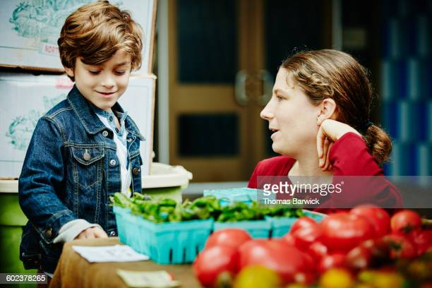Farmer in discussion with boy at farmers market