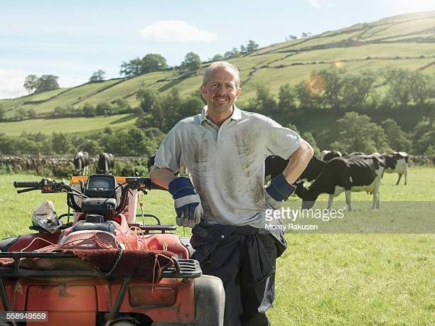 Farmer in field with cows and quadbike