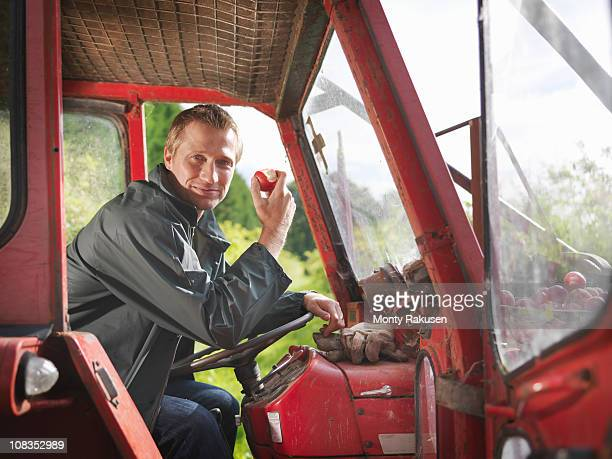 Farmer in tractor eating apple