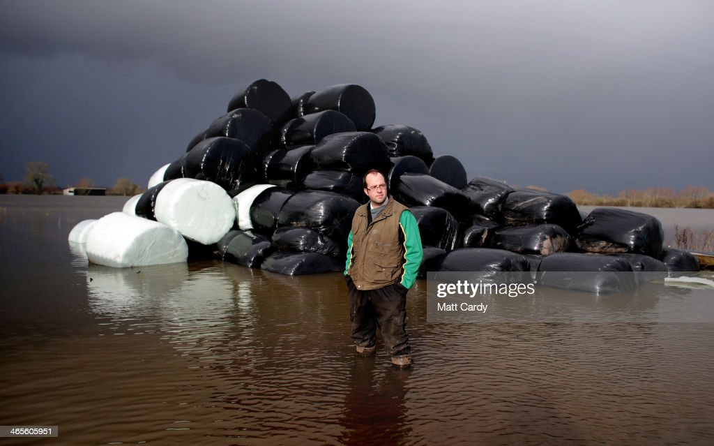 Farmer James Winslade stands in front of bales of animal feed as he surveys flooded land at his farm in Moorland on January 28, 2014 in Somerset, England. The third-generation farmer, whose family has been farming the area for 150 years, calculates 94 percent of his farmland is under water and is still counting the losses from last year's floods when he lost in excess of 160,000 GDP. As Lord Smith, the chairman of the Environment Agency, admits dredging is likely to be part of the plan to reclaim flooded land, an area the size of 40 miles square (65km) of the Somerset Levels remains flooded, causing damage to homes, affecting farmland and even leaving some communities completely cut off.