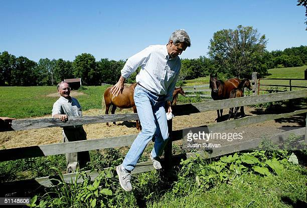 Farmer Jim Nelson watches democratic presidential nominee US Sen John Kerry hops over a fence while visiting the Nelson Family Farm August 6 2004 in...