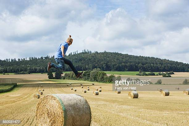 Farmer jumping over hay bale in field