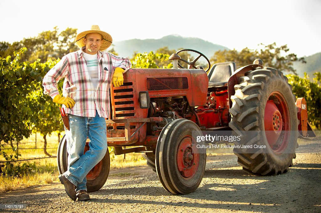 Farmer On Tractor : Farmer leaning on tractor in field stock photo getty images