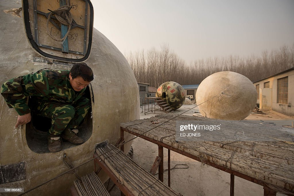 Farmer Liu Qiyuan exits one of seven survival pods that he has also dubbed 'Noah's Arc', in a yard at his home in the village of Qiantun, Hebei province, south of Beijing on December 11, 2012. Inspired by the apocalyptic Hollywood movie '2012' and the 2004 Asian tsunami, Liu hopes that his creations consisting of a fibreglass shell around a steel frame will be adopted by government departments and international organisations for use in the event of tsunamis and earthquakes. Liu has built seven pods which are able to float on water, some of which have their own propulsion. The airtight spheres with varying interiors contain oxygen tanks and seatbelts with space for around 14 people, and are designed to remain upright when in water. AFP PHOTO / Ed Jones