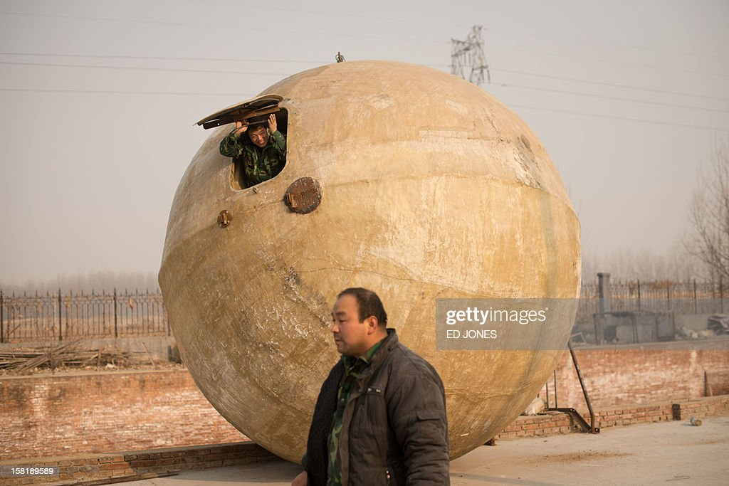 Farmer Liu Qiyuan looks out from inside one of seven survival pods that he has also dubbed 'Noah's Arc', in a yard at his home in the village of Qiantun, Hebei province, south of Beijing on December 11, 2012. Inspired by the apocalyptic Hollywood movie '2012' and the 2004 Asian tsunami, Liu hopes that his creations consisting of a fibreglass shell around a steel frame will be adopted by government departments and international organisations for use in the event of tsunamis and earthquakes. Liu has built seven pods which are able to float on water, some of which have their own propulsion. The airtight spheres with varying interiors contain oxygen tanks and seatbelts with space for around 14 people, and are designed to remain upright when in water. AFP PHOTO / Ed Jones