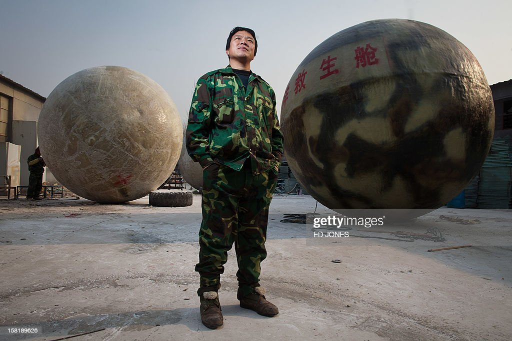 Farmer Liu Qiyuan poses among survival pods that he built and has also dubbed 'Noah's Arc', in a yard at his home in the village of Qiantun, Hebei province, south of Beijing on December 11, 2012. Inspired by the apocalyptic Hollywood movie '2012' and the 2004 Asian tsunami, Liu hopes that his creations consisting of a fibreglass shell around a steel frame will be adopted by government departments and international organisations for use in the event of tsunamis and earthquakes. Liu has built seven pods which are able to float on water, some of which have their own propulsion. The airtight spheres with varying interiors contain oxygen tanks and seatbelts with space for around 14 people, and are designed to remain upright when in water. AFP PHOTO / Ed Jones