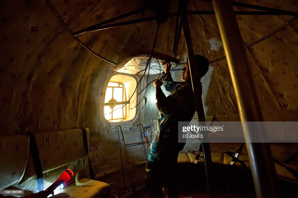 Farmer Liu Qiyuan secures a hatch inside one of seven survival pods that he has also dubbed 'Noah's Arc', in a yard at his home in the village of Qiantun, Hebei province, south of Beijing on December 11, 2012. Inspired by the apocalyptic Hollywood movie '2012' and the 2004 Asian tsunami, Liu hopes that his creations consisting of a fibreglass shell around a steel frame will be adopted by government departments and international organisations for use in the event of tsunamis and earthquakes. Liu has built seven pods which are able to float on water, some of which have their own propulsion. The airtight spheres with varying interiors contain oxygen tanks and seatbelts with space for around 14 people, and are designed to remain upright when in water. AFP PHOTO / Ed Jones