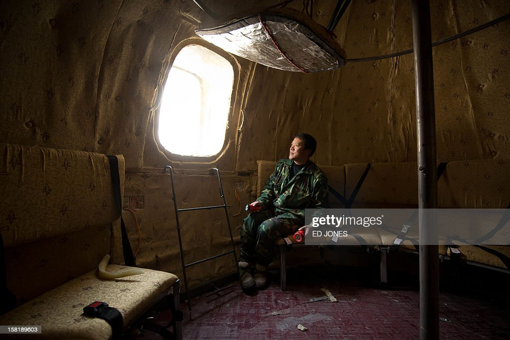 Farmer Liu Qiyuan sits inside one of seven survival pods that he has also dubbed 'Noah's Arc', in a yard at his home in the village of Qiantun, Hebei province, south of Beijing on December 11, 2012. Inspired by the apocalyptic Hollywood movie '2012' and the 2004 Asian tsunami, Liu hopes that his creations consisting of a fibreglass shell around a steel frame will be adopted by government departments and international organisations for use in the event of tsunamis and earthquakes. Liu has built seven pods which are able to float on water, some of which have their own propulsion. The airtight spheres with varying interiors contain oxygen tanks and seatbelts with space for around 14 people, and are designed to remain upright when in water. AFP PHOTO / Ed Jones