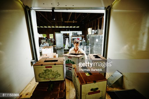 Farmer loading produce boxes into truck
