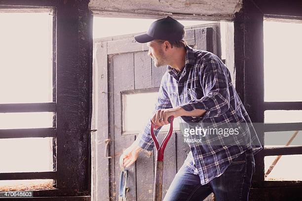 Farmer looking away while closing barn door