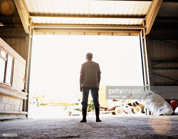 Farmer looking out from inside barn