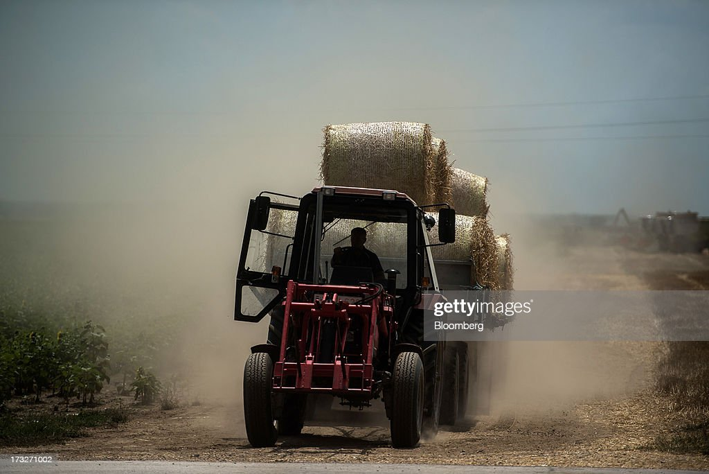 A farmer moves a wagon of hay bales from a field operated by Bonafarm Group in Kislippo, Hungary, on Wednesday, July 10, 2013. The world's grain harvest will be bigger in the 2013-14 season than predicted a month ago on increased estimates for corn in China and larger wheat crops in India and Canada, the International Grains Council said. Photographer: Akos Stiller/Bloomberg via Getty Images