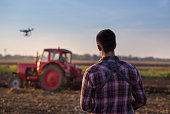 Young farmer navigating drone above farmland. High technology innovations for increasing productivity in agriculture
