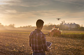 Attractive farmer navigating drone above farmland with silos and tractor in background. High technology innovations for increasing productivity in agriculture