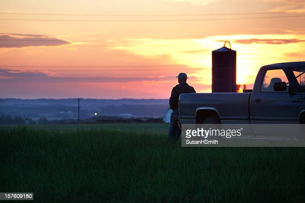 A farmer on his truck watching a sunset