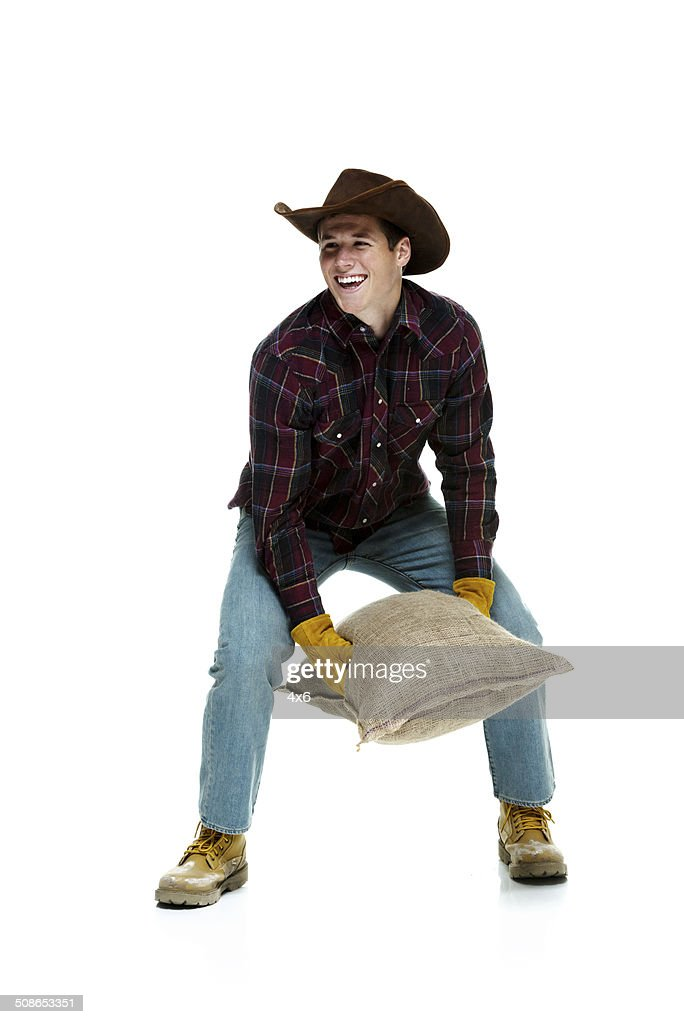 Farmer picking up a burlap sack : Stock Photo