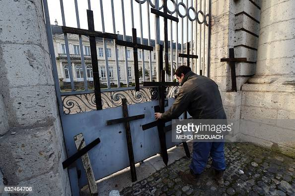 TOPSHOT A farmer places wooden crosses in front of the entrance of the prefecture during a demonstration against the hundreds of suicides of French...