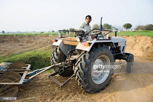 Farmer ploughing a field with a tractor, Farrukh Nagar, Gurgaon, Haryana, India
