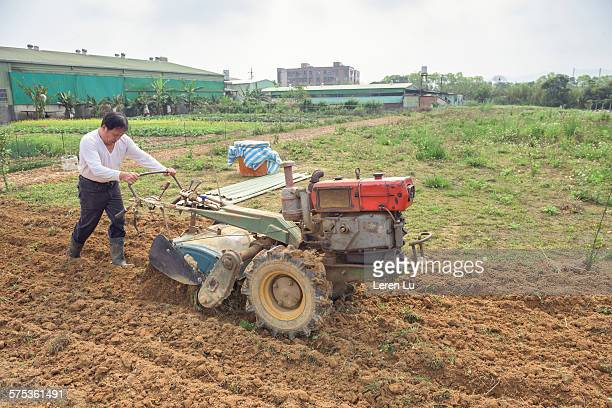 Farmer plowing with ploughing machine