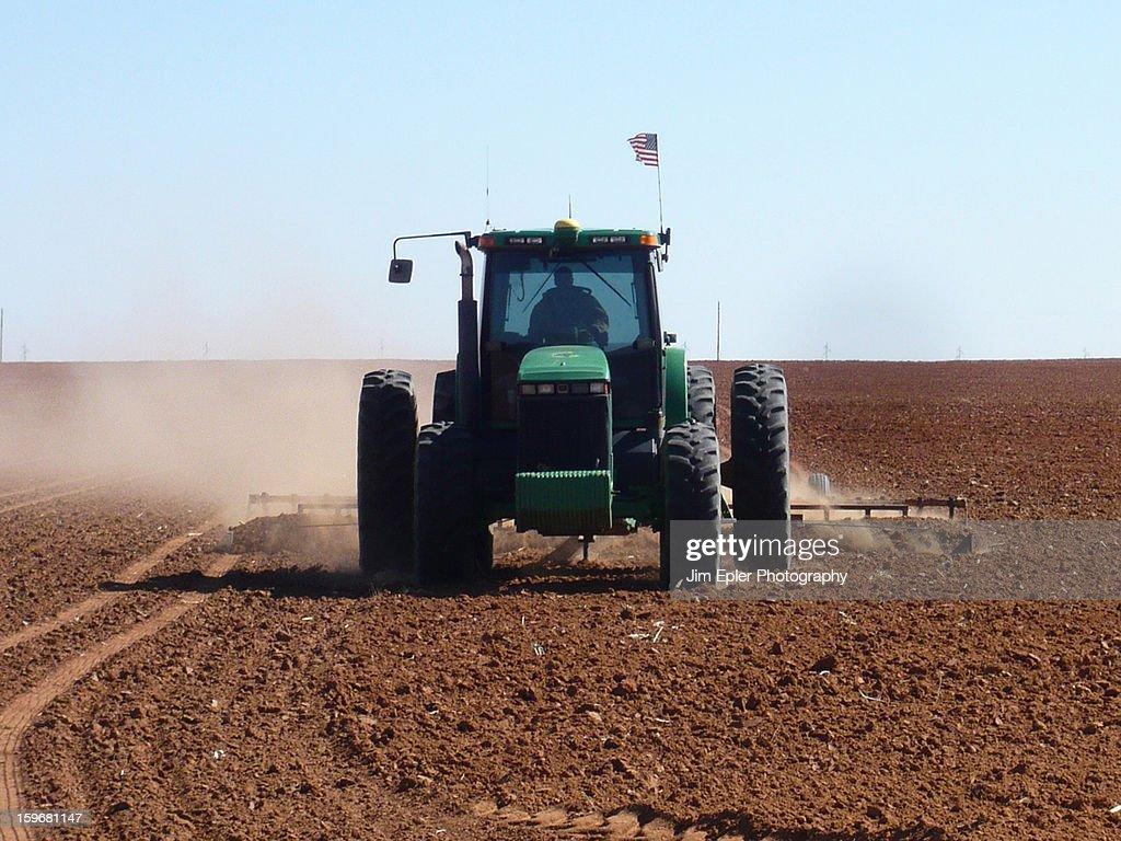 CONTENT] A farmer plows a field on a farm in Texas. An patriotic American flag can be seen mounted on the equipment cab.