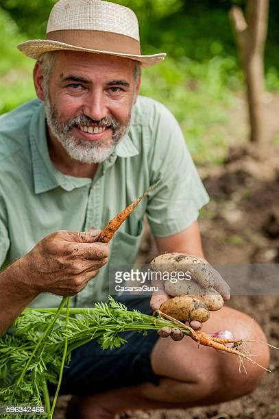 Farmer Posing With Hands Full of Vegetables