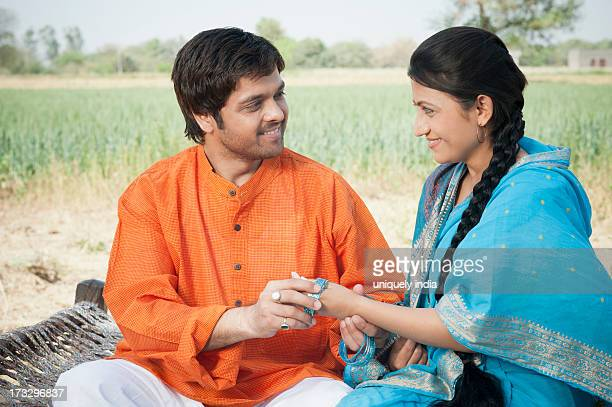 Farmer putting on bangles in his wife hand, Sohna, Haryana, India