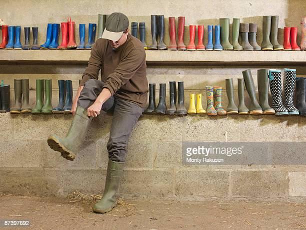 Farmer Putting On Wellington Boots