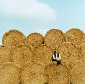 Farmer Relaxing on Hay Bales, Looking at the Camera