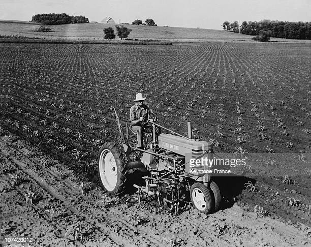 A farmer rides his John Deere tractor in his corn field in the United States