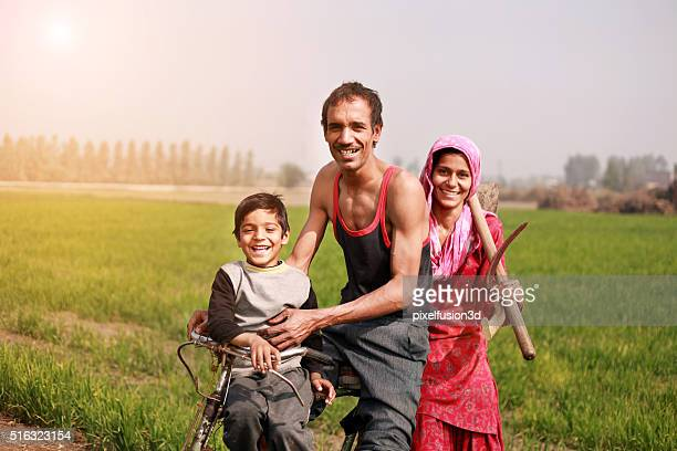 Farmer riding cycle to the field with his family