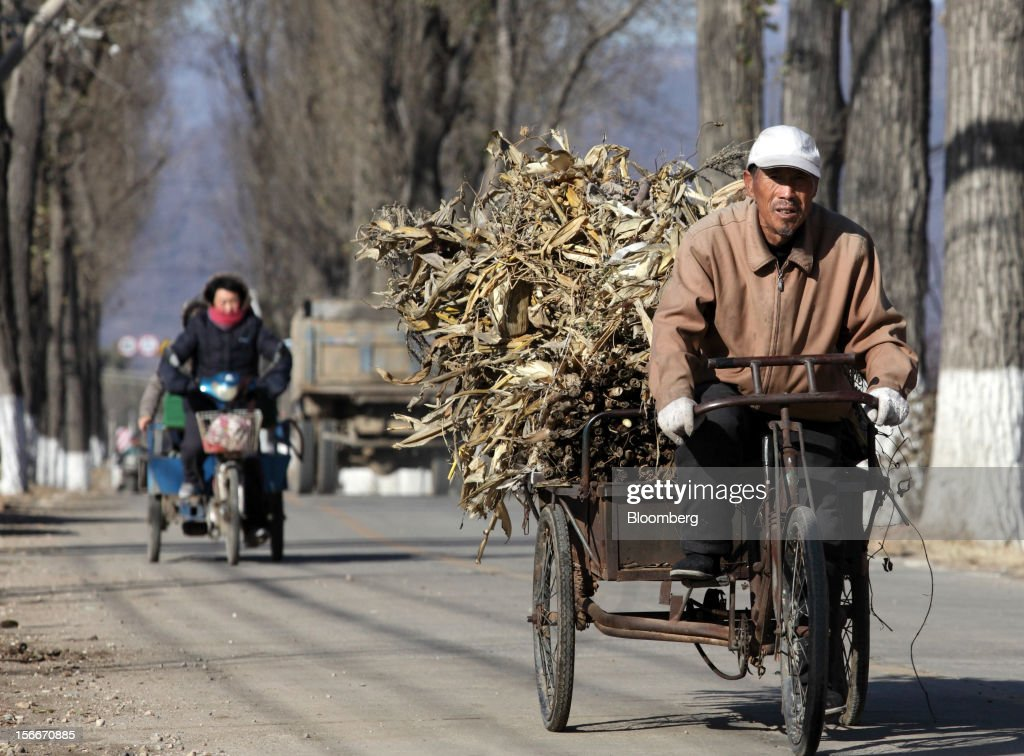A farmer, right, cycles on a road in Pinggu, on the outskirts of Beijing, China, on Saturday, Nov. 17, 2012. China's gross domestic product slowed to 7.4 percent in the July-September period from a year earlier, the weakest in three years. Photographer: Tomohiro Ohsumi/Bloomberg via Getty Images