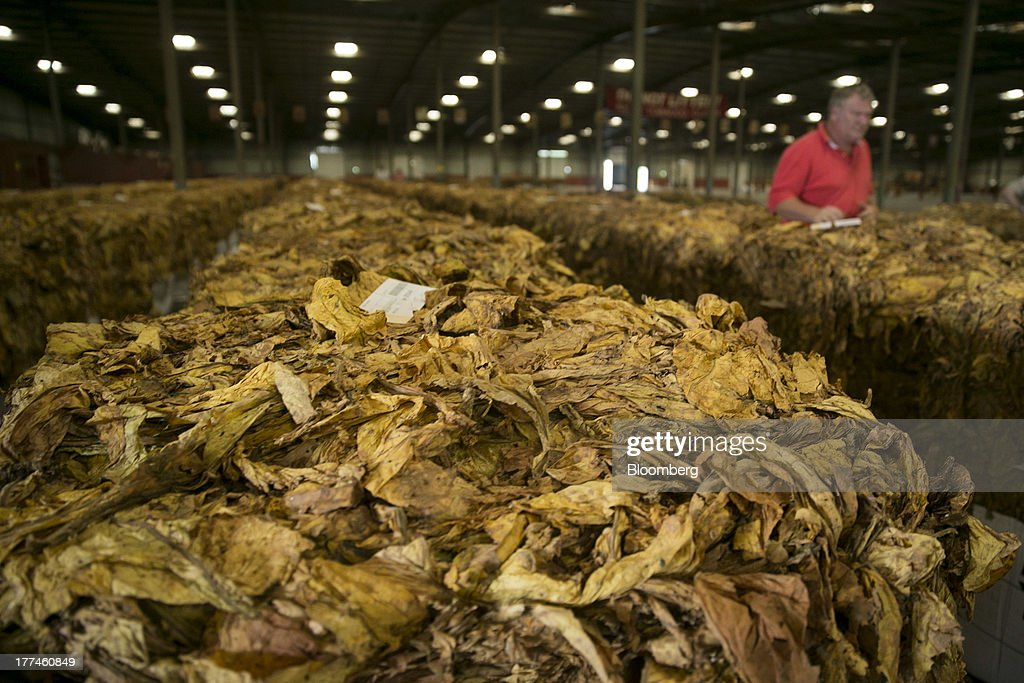 Farmer Roy Cook, back right, reviews tobacco bales following an auction at the Old Belt Tobacco Sales warehouse in Rural Hall, North Carolina, U.S., on Tuesday, Aug. 20, 2013. President Barack Obama's proposal in April to raise federal excise taxes on cigarettes by about 93%, to $1.95 a pack, is not likely to gain political support, due in part to weak consumer spending amid sluggish wage growth in recent years. Photographer: Andrew Harrer/Bloomberg via Getty Images
