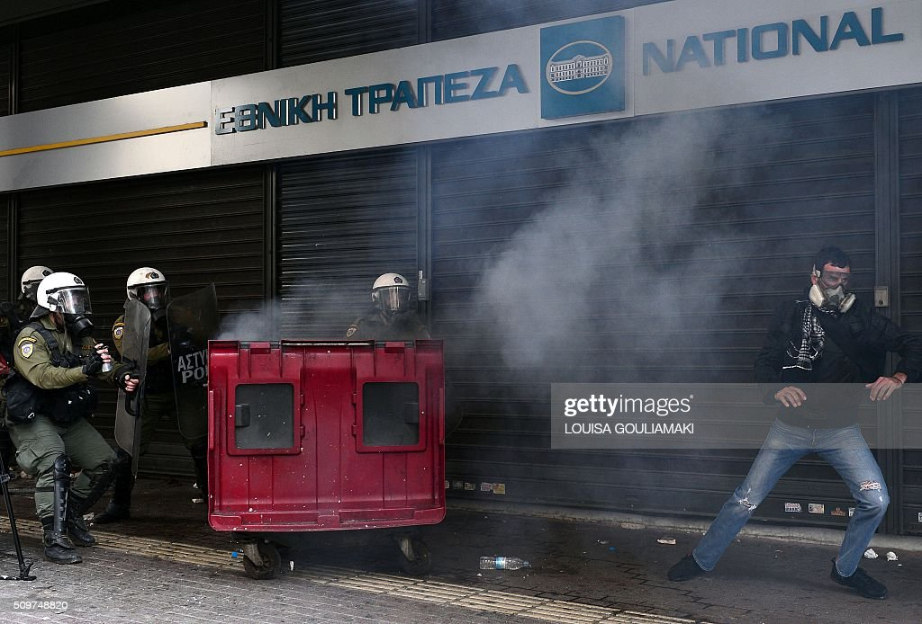 A farmer runs from police in front of the Agriculture ministry in Athens during a demonstration against the pension reform on February 12, 2016. Fears that Greece will exit the eurozone, a 'Grexit', could revive if Greek authorities do not come up with 'credible' reforms, notably on pensions, a senior IMF official said February 11, 2016. / AFP / LOUISA GOULIAMAKI