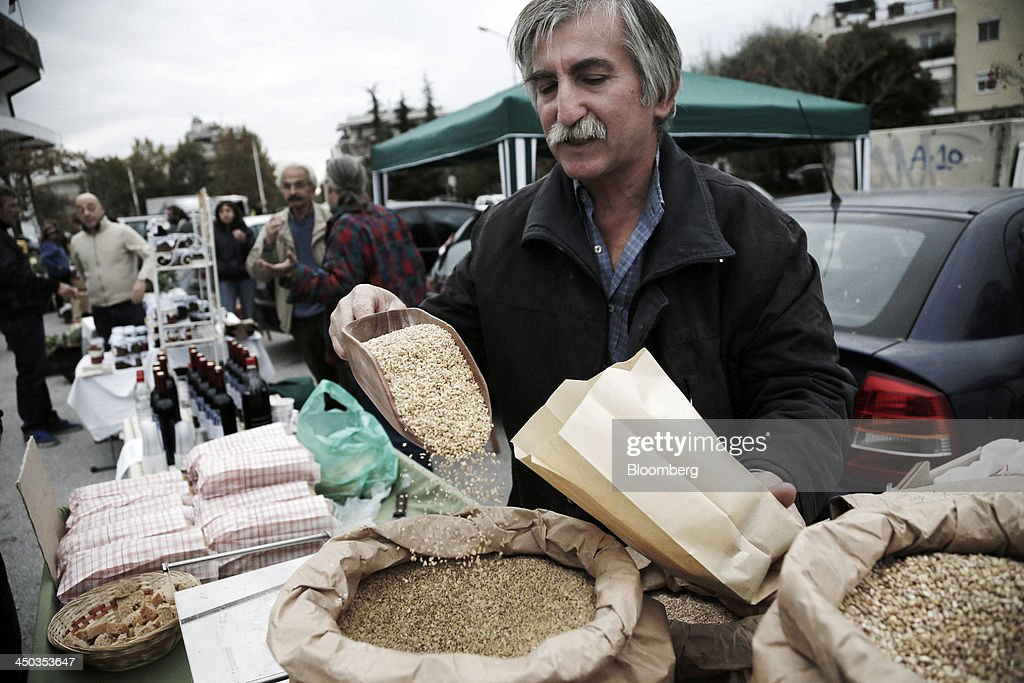 A farmer scoops bulgar wheat into a paper bag at a farmers' market in Thessaloniki, Greece, on Saturday, Nov. 16, 2013. Greek Prime Minister Antonis Samaras, who survived a no-confidence vote on Nov. 11 with his parliamentary majority reduced to four, is trumpeting the first economic growth in seven years for 2014. Photographer: Konstantinos Tsakalidis/Bloomberg via Getty Images