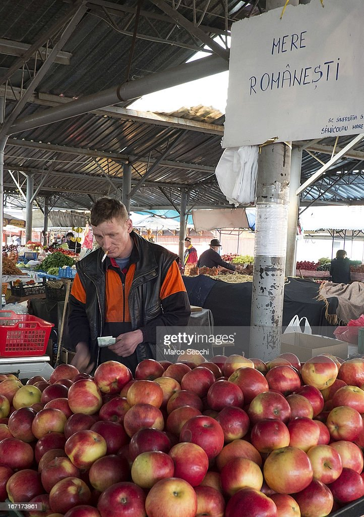 A farmer sells Romanian apples from his stall at the daily market on April 21, 2013 in Timisoara, Romania. Romania has abandoned a target deadline of 2015 to switch to the single European currency and will now submit to the European Commission a programme on progress towards the adoption of the Euro, which for the first time will not have a target date.