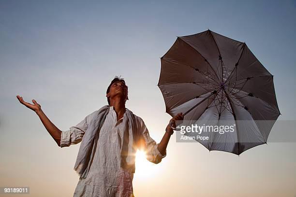 Farmer sheltering from sun hoping for monsoon rain