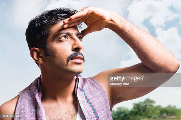 Farmer shielding his eyes