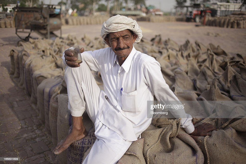 A farmer sits on sacks of wheat at a grain market in the district of Jalandhar in Punjab, India, on Tuesday, April 16, 2013. Wheat harvest in India, the second-biggest grower, may reach a record for a sixth straight year after farmers increased use of high-yielding seeds and winter rains boosted crop prospects, a state-run researcher said. Photographer: Prashanth Vishwanathan/Bloomberg via Getty Images