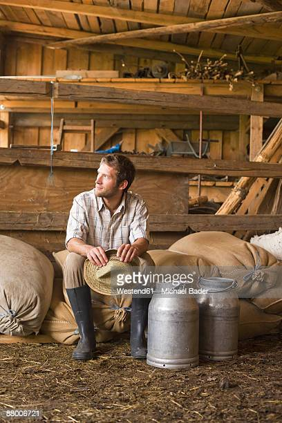Farmer sitting in barn with milk cans, looking away