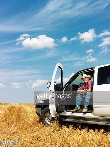 Farmer Sitting in Truck in a Field