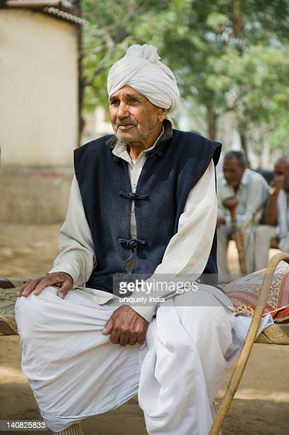 Farmer sitting on a cot, Hasanpur, Haryana, India