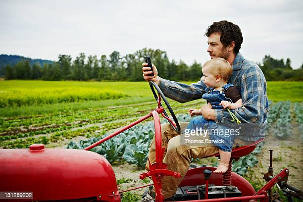 Farmer sitting on tractor looking at smart phone