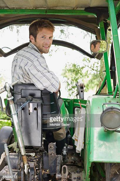 Farmer sitting in tractor, smiling, portrait