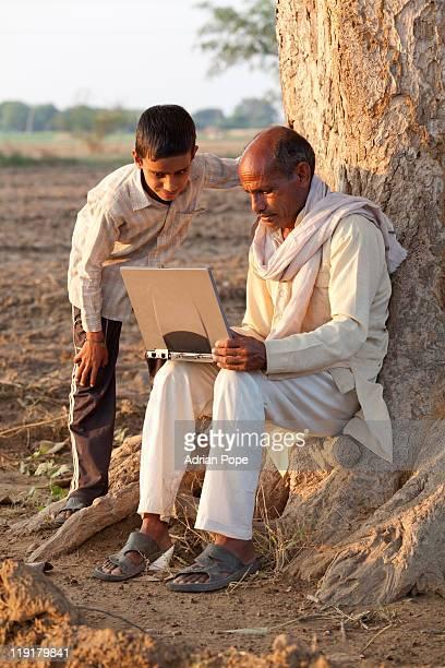 Farmer & son looking at laptop