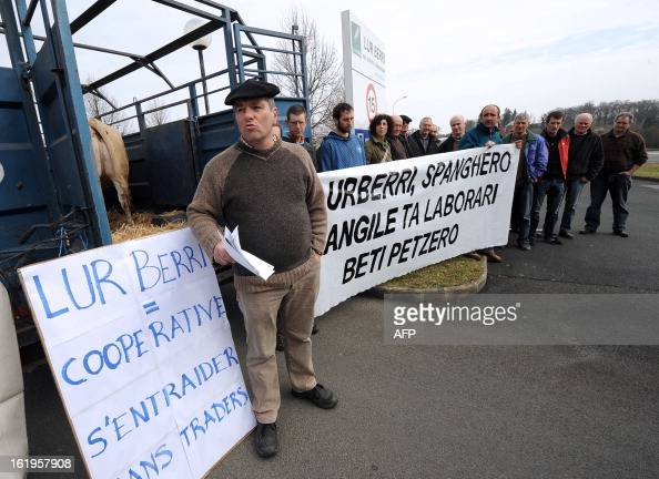 A farmer speaks next to a banner written in the Basque language and reading 'Lur Berri Spanghero employees and farmers are always cheated' as he...