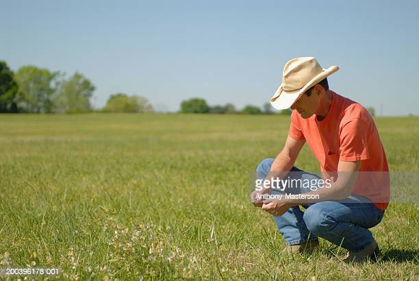 Farmer squatting in field
