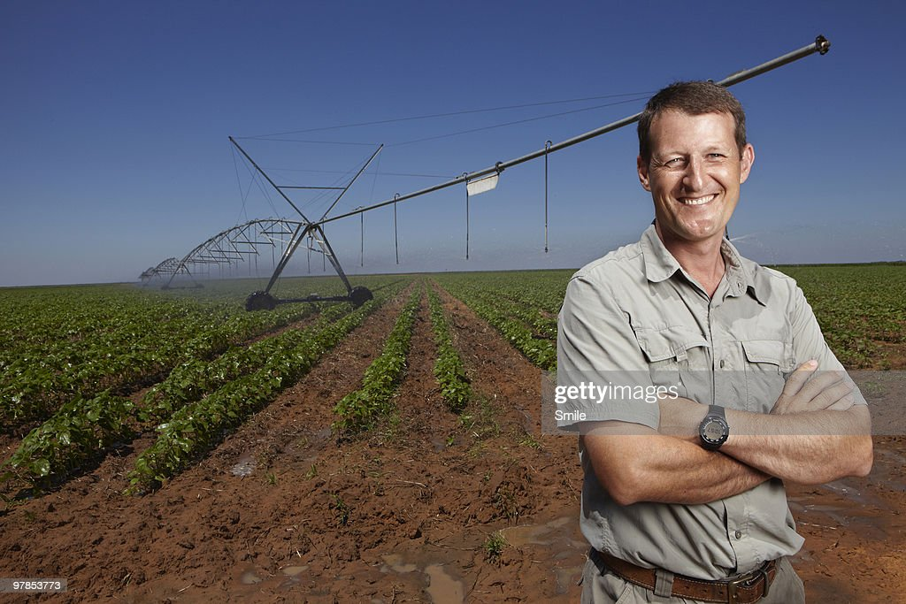 Farmer standing in field smiling : Stock Photo