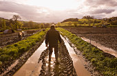 Farmer standing in muddy puddles